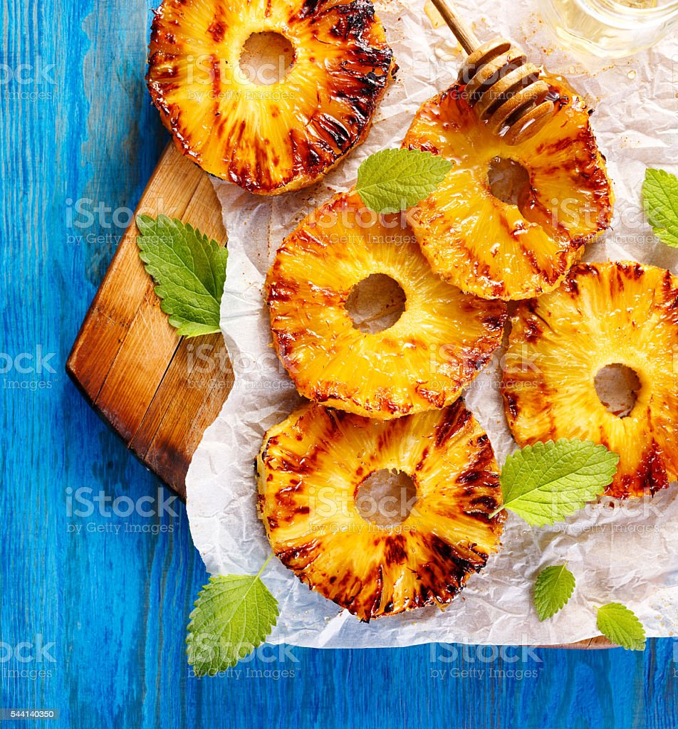 Grilled pineapple slices with addition of honey, top view stock photo