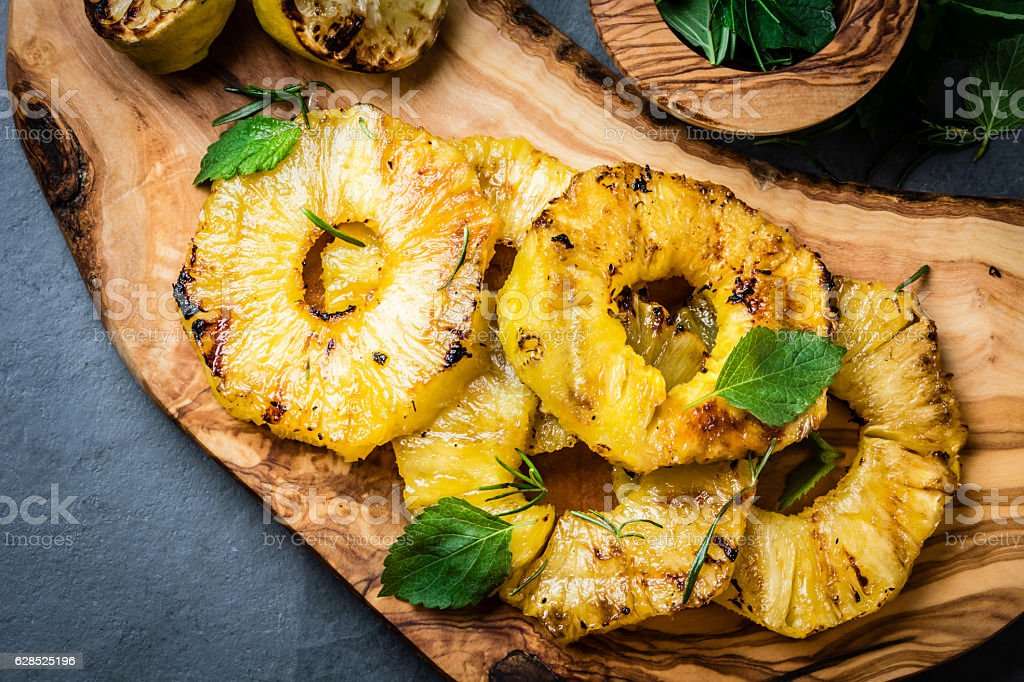 Grilled pineapple slices with fresh mint on olive cutting board stock photo