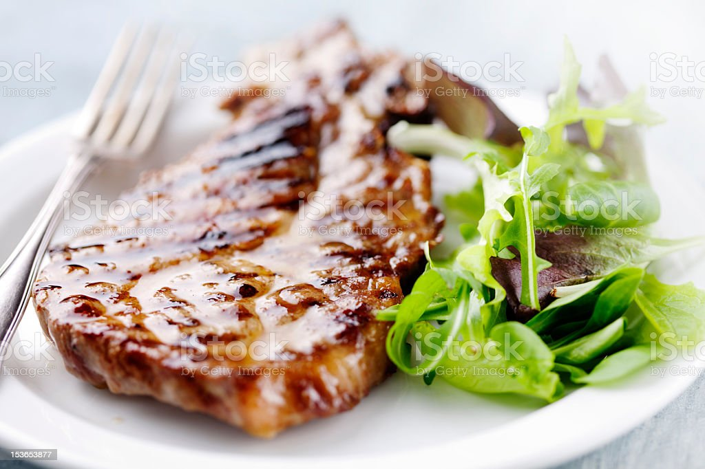 Grilled pork chop and salad greens on a white plate stock photo
