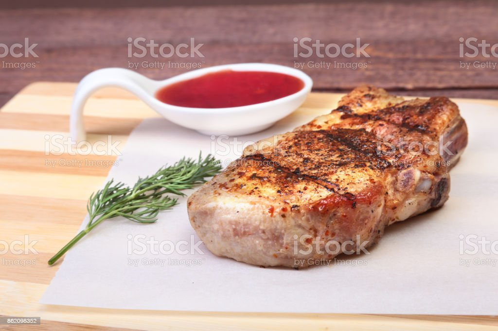 grilled pork chop with Cranberry sauce on plate on wooden board stock photo