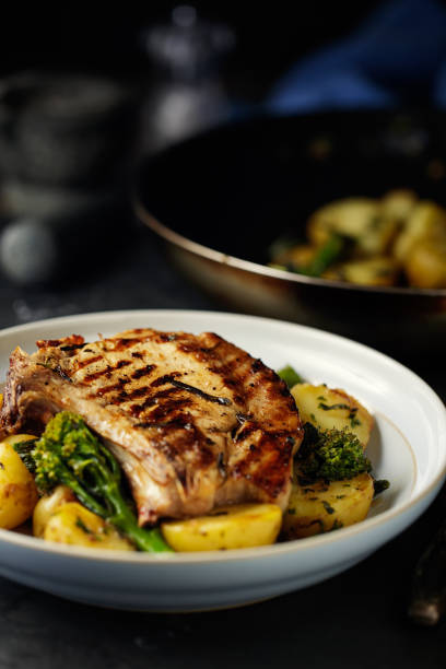 gegrilltes kotelett mit knoblauch anbraten kartoffeln - gegrilltes schweinekoteletts stock-fotos und bilder