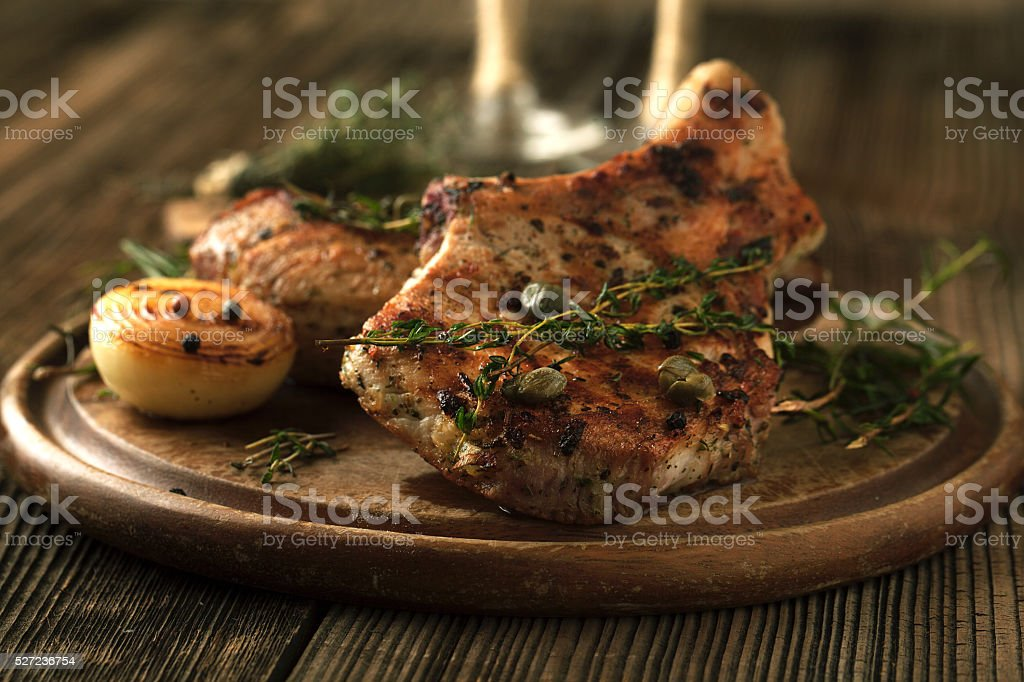 Grilled pork chop with spices, garlic and onions. stock photo