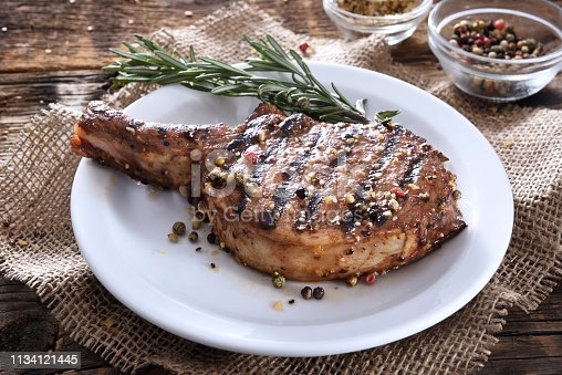 Juicy grilled pork chop with spices on a white plate