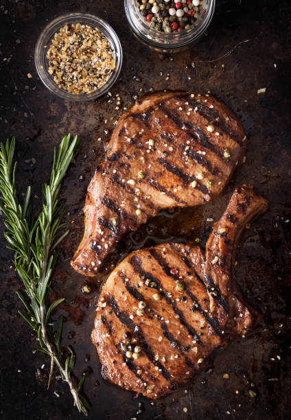 Grilled pork chops with spices Two juicy grilled pork chops with spices an peppers on a dark background pork stock pictures, royalty-free photos & images