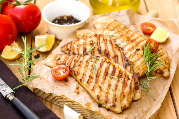 grilled pork escalopes with rosemary and cherry tomatoes - escalope imagens e fotografias de stock