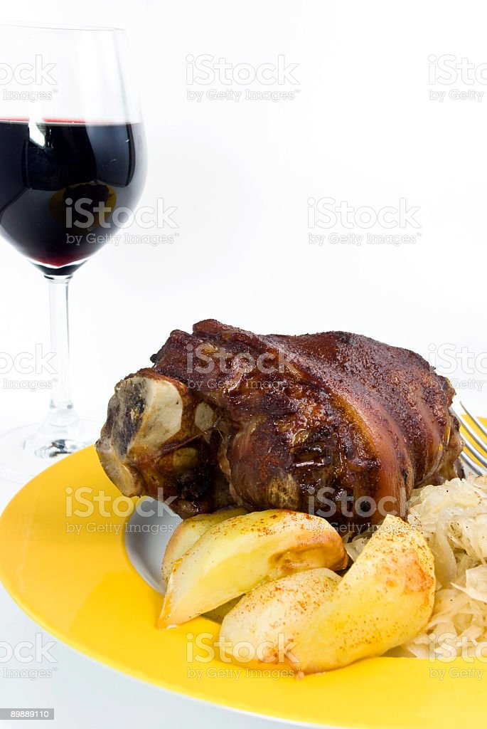 grilled pork knuckle with deep fried potatoes,sauerkraut and wine royalty-free stock photo