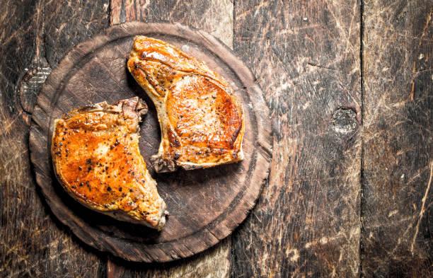 gegrilltes schweinefleisch auf einer cutting board. - gegrilltes schweinekoteletts stock-fotos und bilder