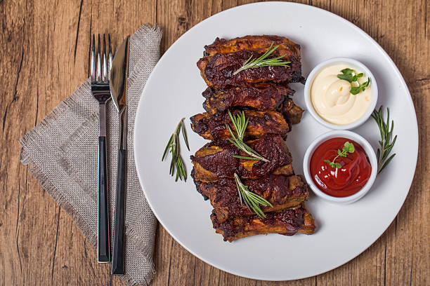 Grilled pork ribs in barbecue sauce Grilled pork ribs in barbecue sauce on white plate top view human rib cage stock pictures, royalty-free photos & images