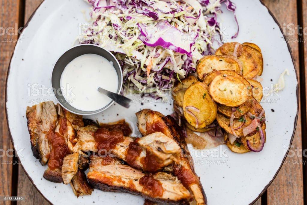 Costillas de cerdo a la parrilla, verduras y salsa a la mesa de madera, vista superior - foto de stock
