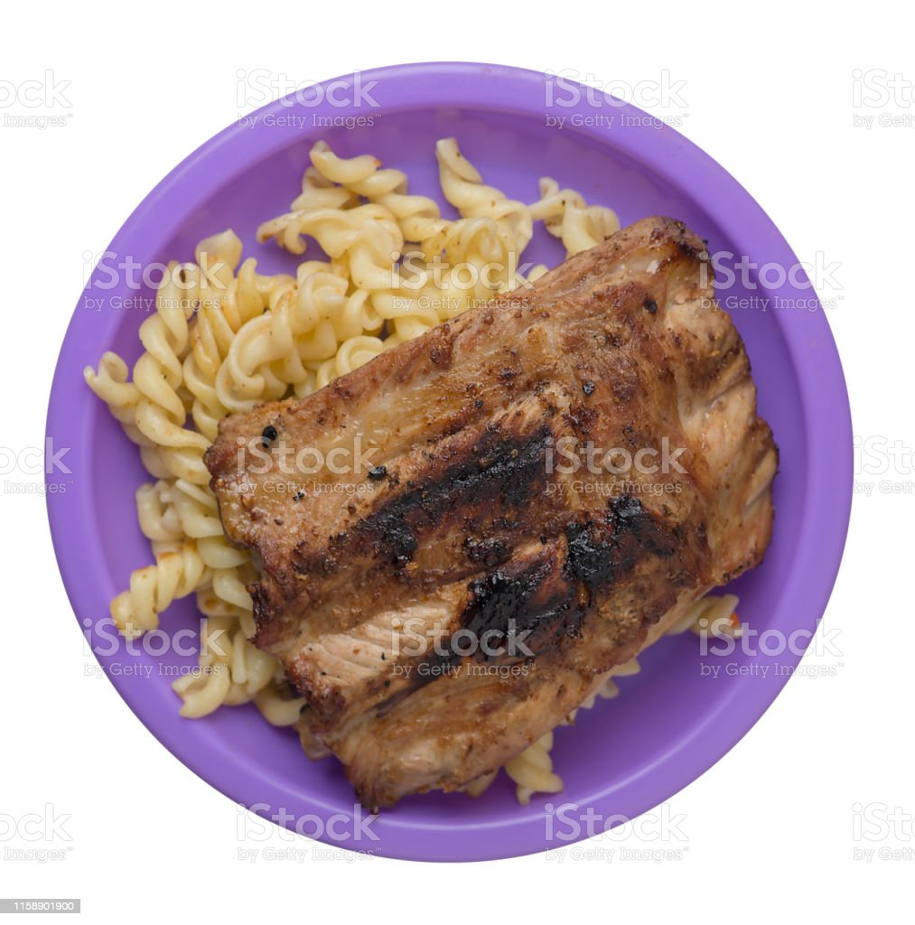 grilled pork ribs with pasta. grilled pork ribs on a purple plate...