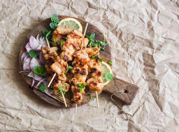 gegrillte schweinefleisch-spieße mit eingelegten roten zwiebeln und minze auf einem rustikalen schneidebrett auf papierhintergrund. köstliche sommer mittagessen. gesunde ernährung-konzept - marinade für grillfleisch stock-fotos und bilder