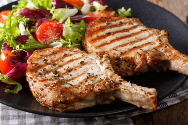 Grilled pork steak with bone and fresh salad close-up. horizontal Grilled pork steak with bone and fresh salad close-up on a plate. horizontal pork stock pictures, royalty-free photos & images