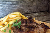 Tasty grilled pork steak with french fries and oregano over wooden background