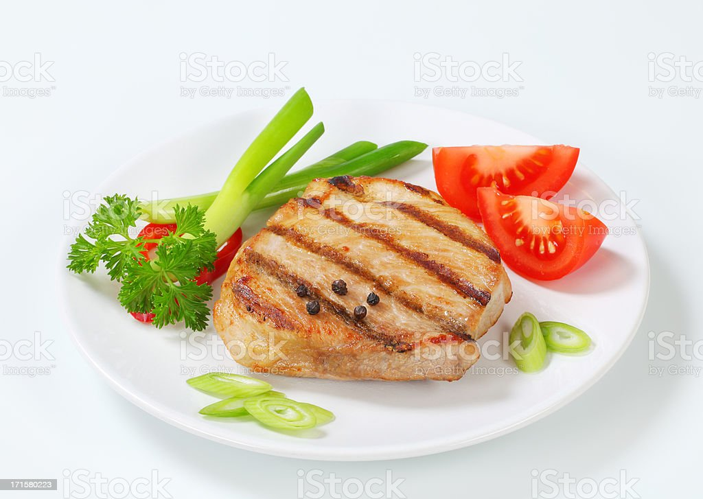 grilled pork steak with vegetable garnish on a plate stock photo