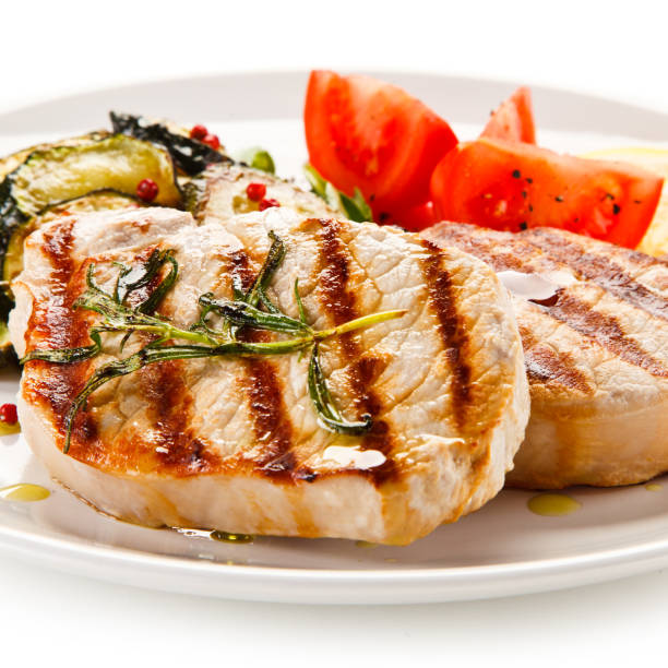 Grilled pork steak with vegetables on white background stock photo