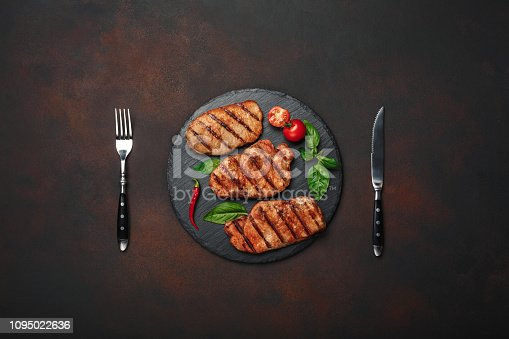 655794674istockphoto Grilled pork steaks with basil, tomatoes, knife and fork on black stone and brown rusty background 1095022636