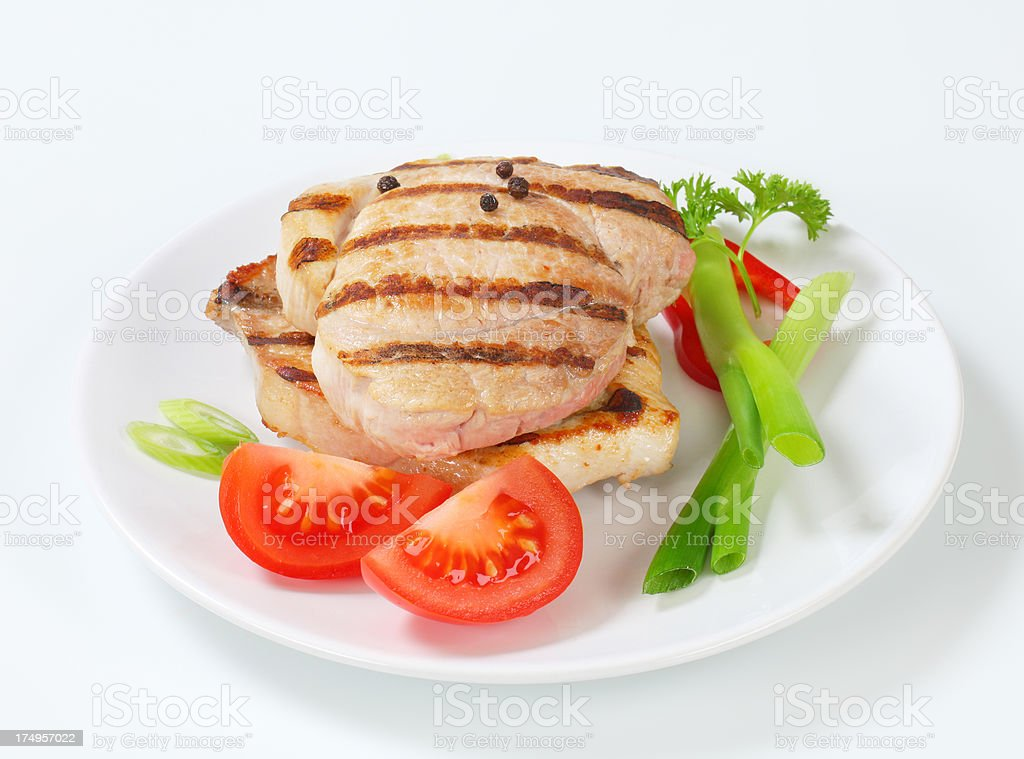 grilled pork steaks with vegetable garnish on a plate royalty-free stock photo