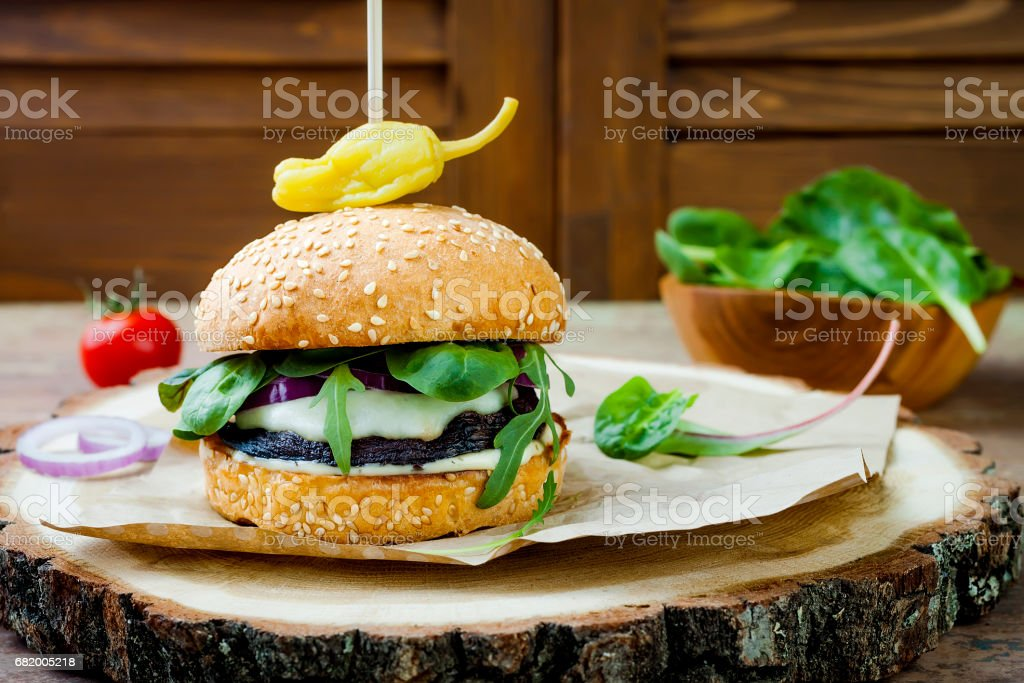 Grilled portobello mushroom burger. Healthy veggies hamburger with onions, arugula, cheese, spicy pickled hot peppers and tartar sauce. Copy space stock photo