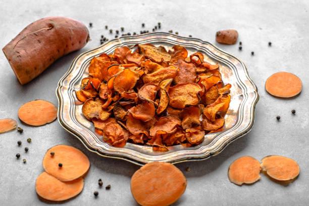 gegrillte kartoffel-chips mit süßkartoffeln, gebackenes gericht, vegane oder vegetarische speisen-konzept - gemüsechips stock-fotos und bilder