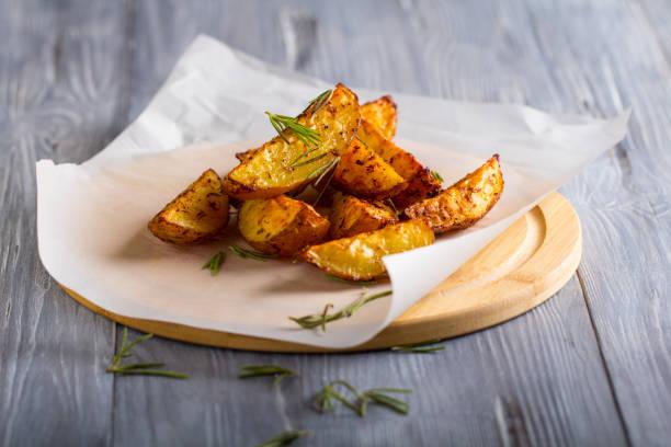 烤土豆迷迭香木背景 - 薯仔食品 個照片及圖片檔