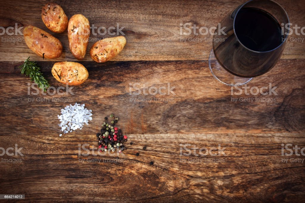 Grilled potatoes with spices on old wood stock photo