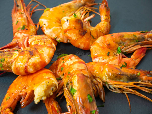 Grilled prawns, grilled shrimps with sauce and herbs, fresh grilled shellfish on a slate plate for appetizers stock photo