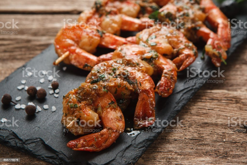 Grilled prawns on black slate. Mediterranean food. stock photo