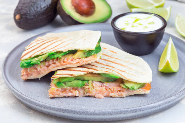 Grilled quesadilla with smoked salmon and avocado served with yogurt and lime dip, on gray plate, horizontal stock photo