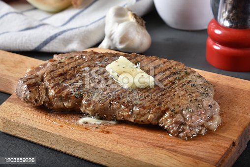A juicy grilled rib steak with a pat of butter melting on top