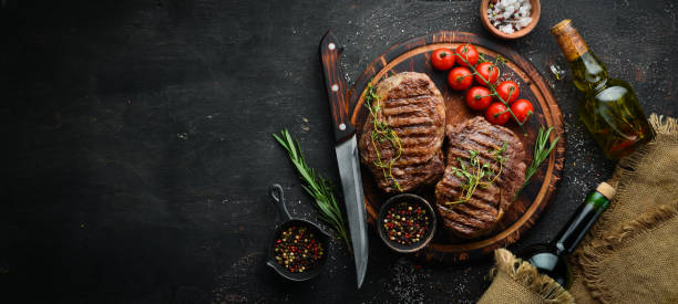 Bife, ervas e especiarias grelhados da carne do Ribeye em uma tabela escura. Vista de cima. Espaço livre para o seu texto. - foto de acervo