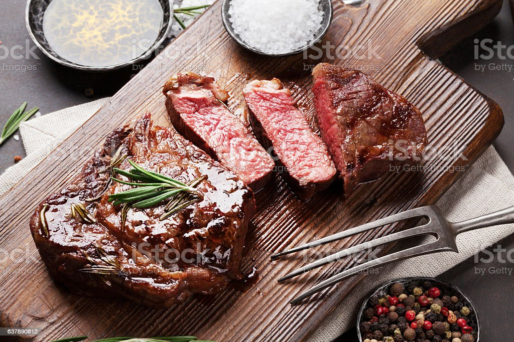 Grilled ribeye beef steak, herbs and spices - foto de acervo
