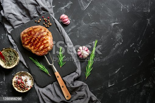 808351106 istock photo Grilled ribeye beef steak on the fork, black stone background. Top view, flat lay, copy space. 1255956295