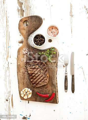 655794674istockphoto Grilled ribeye beef steak with herbs and spices on walnut 498556962