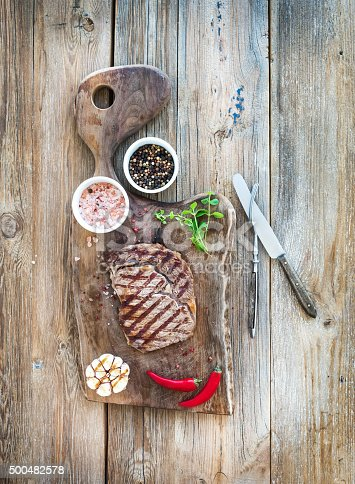 655794674istockphoto Grilled ribeye beef steak with herbs and spices on walnut 500482578