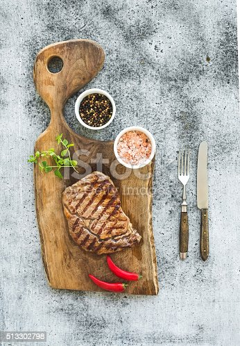808351094 istock photo Grilled ribeye beef steak with herbs and spices on walnut 513302798