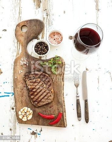 808351094istockphoto Grilled ribeye beef steak with herbs, spices  and glass of 519624584