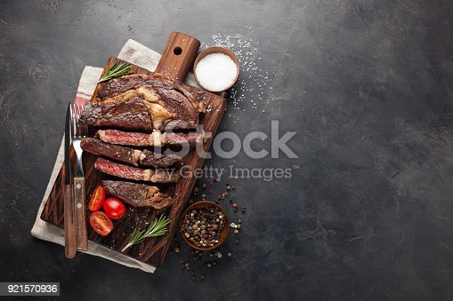 istock Grilled ribeye beef steak with red wine, herbs and spices on a dark stone background. Top view with copy space for your text 921570936