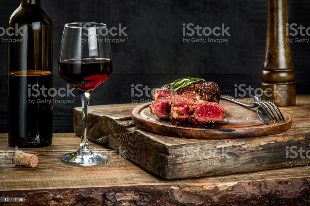 Grilled ribeye beef steak with red wine, herbs and spices on wooden table stock photo