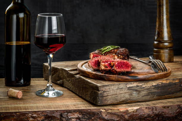 Grilled ribeye beef steak with red wine, herbs and spices on wooden table Grilled ribeye beef steak with red wine, herbs and spices on wooden table. Still life human rib cage stock pictures, royalty-free photos & images