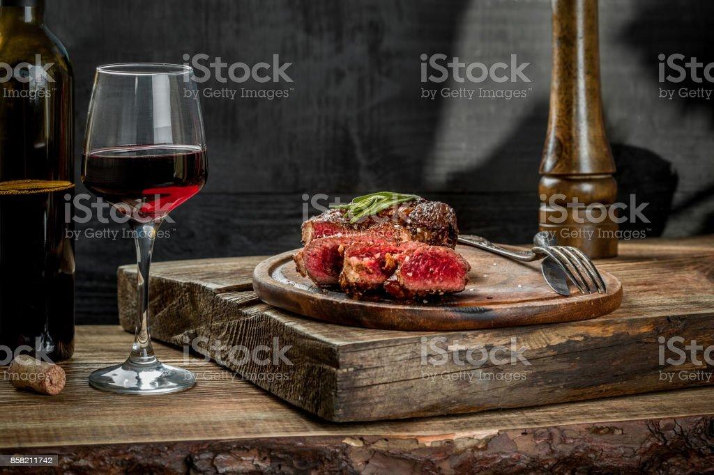 Gegrilde ribeye biefstuk met rode wijn, kruiden en specerijen op de houten tafel foto