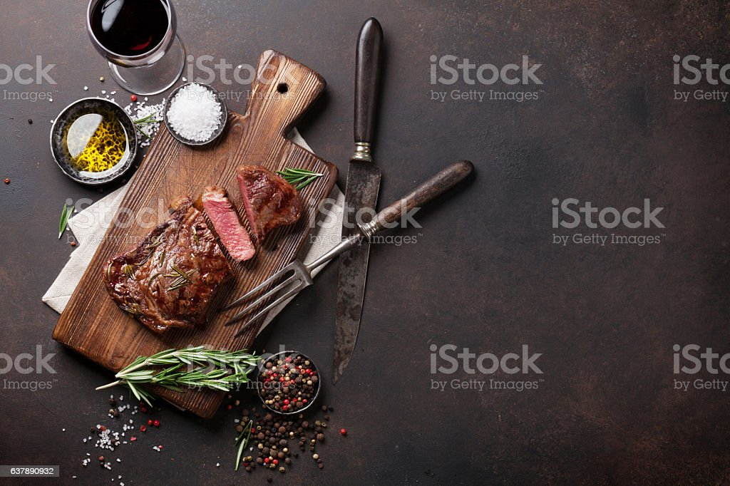 Grilled ribeye beef steak with red wine, herbs and spices - foto de acervo