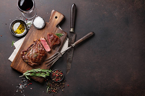 Grilled ribeye beef steak with red wine, herbs and spices - foto de stock