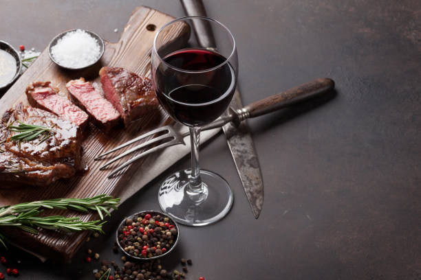Grilled ribeye beef steak with red wine, herbs and spices Grilled ribeye beef steak with red wine, herbs and spices on stone table red wine stock pictures, royalty-free photos & images