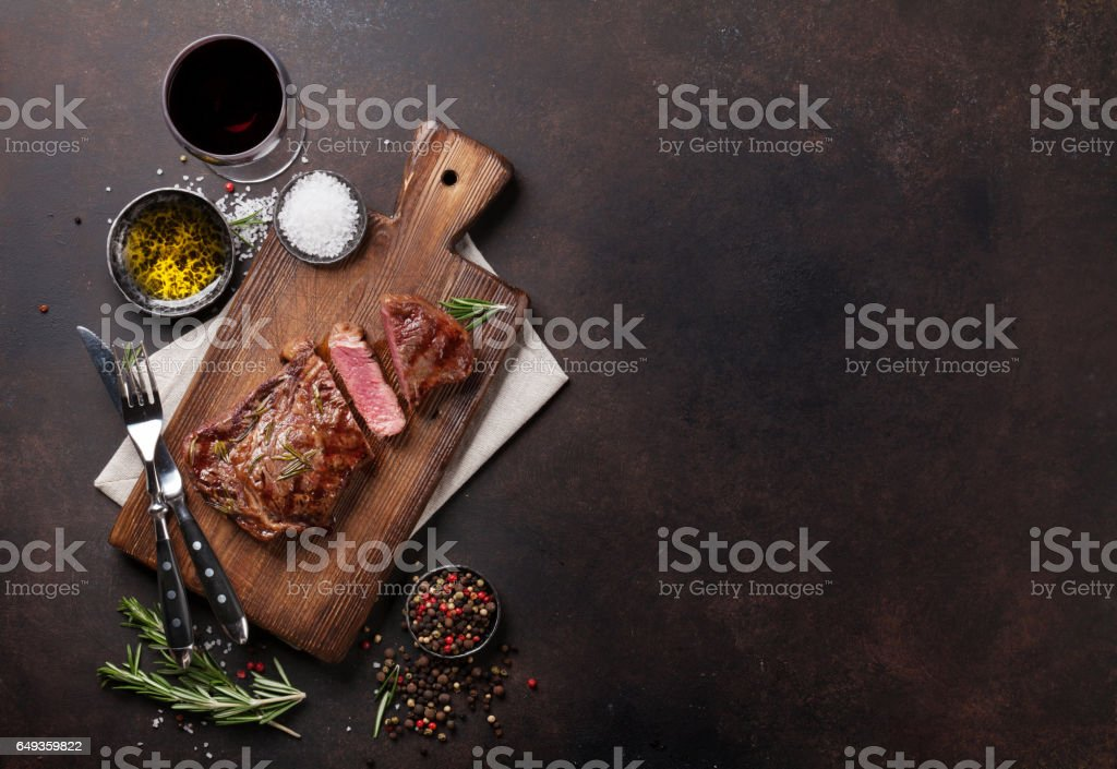 Grilled ribeye beef steak with red wine, herbs and spices stock photo