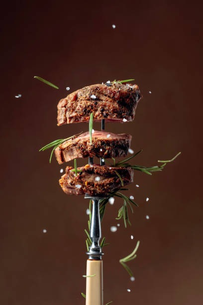 Grilled ribeye beef steak with rosemary on a brown background. stock photo