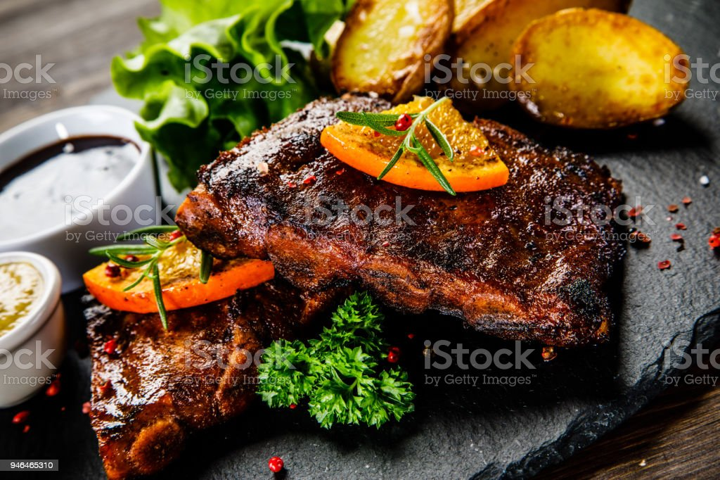 Grilled ribs, boiled potatoes and vegetables on wooden background stock photo