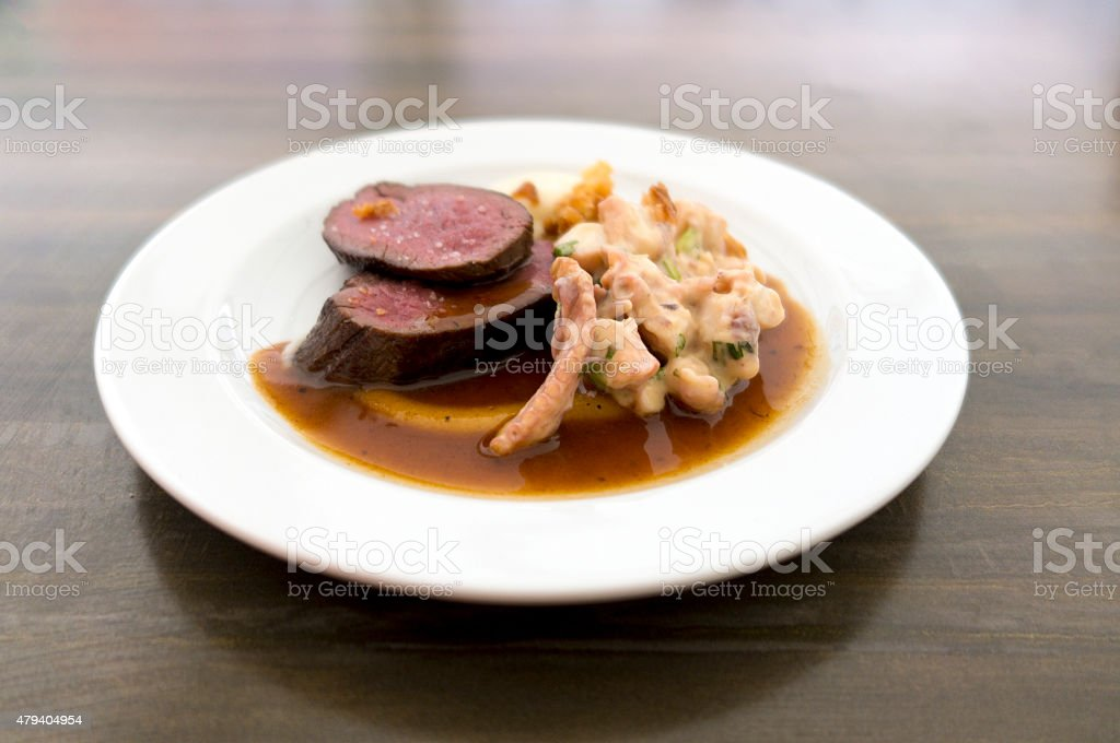 Grilled saddle of deer, grilled octopus, dressing of orange and pink ginger stock photo