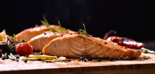 grilled salmon fish and various vegetables on wooden table on black background - cortado em filete imagens e fotografias de stock