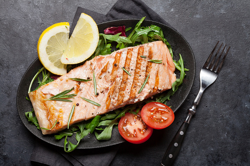 Grilled salmon fish fillet with salt, pepper and rosemary over salad leaves. On stone table. Top view flat lay