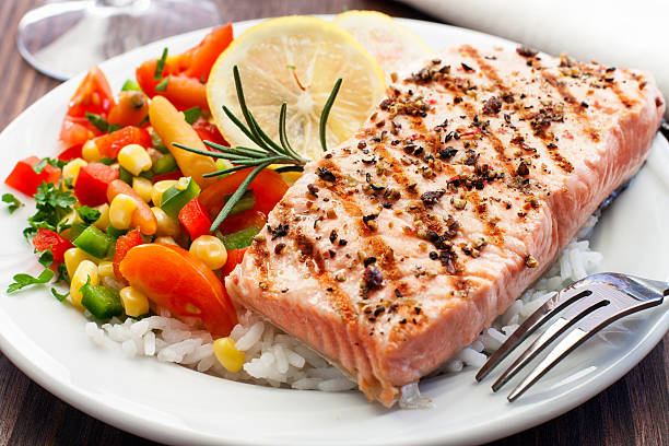 a grilled salmon followed by fresh rice and vegetables - gestoomd stockfoto's en -beelden